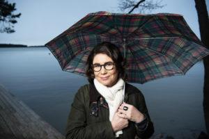 Marjo Heiskanen - kirjailija sateenvarjon alla meren rannassa