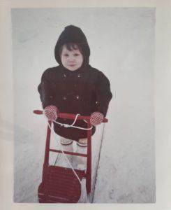 Marjo lapsena potkukelkan kanssa