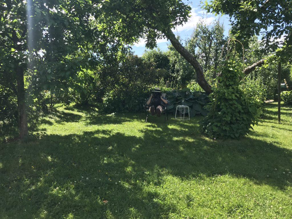 Kirjailija Marjo Heiskanen lepäilee puutarhassaan koiransa kanssa.
